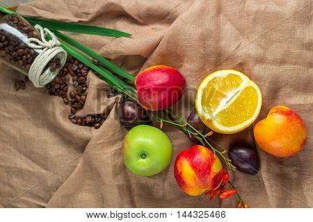 Still life on sackcloth background: apple peaches orance plums
