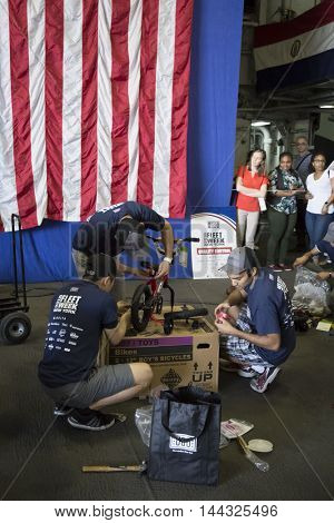 NEW YORK MAY 26 2016: USO volunteers and Navy personnel assemble bicycles for children of the crew in the hangar bay of the USS Bataan (LDH 5) at the Build-A-Bike event for Fleet Week 2016.