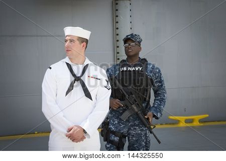 NEW YORK MAY 26 2016: US Navy security personnel stand ready at the USS Bataan (LDH 5) an amphibious assault ship moored at Pier 88 for Fleet Week NY 2016.