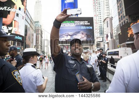 NEW YORK MAY 26 2016: Member of the NYPD takes a selfie with US Navy Sailors and Marines at the Armed Forces Recruiting Station on Military Island Pedestrian Plaza in Times Square for Fleet Week NY.