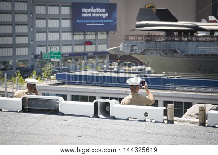 NEW YORK MAY 26 2016: Two US Marines on the flight deck of the USS Bataan (LDH 5) an amphibious assault ship moored at Pier 88 for Fleet Week NY 2016.