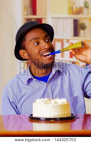 Charming man wearing blue shirt and hat sitting by table with birthday cake in front, blowing party horn celebrating alone smiling.