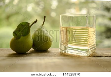 pear and a glass of juice on a wooden table in the garden background. close-up