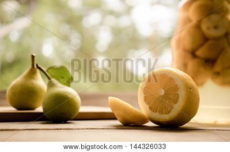 pear, lemon and banks with compote on a wooden table in the garden background. close-up