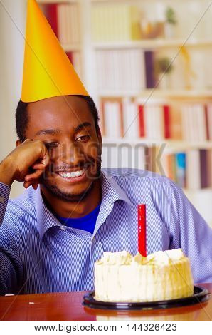 Good looking man wearing blue shirt and hat sitting by table with cake in front, single candle burning, skeptically smiling, celebrating alone concept.