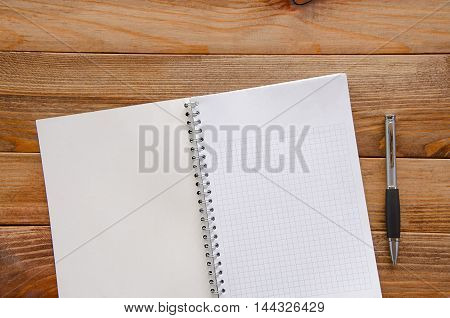 Pen with white paper on a wooden table