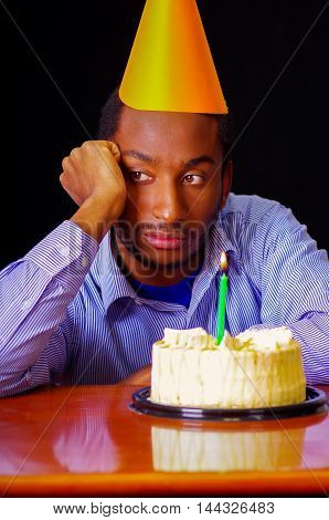 Sad man wearing blue shirt and hat sitting by table with cake in front, single candle burning, looking bored depressed, celebrating alone concept.