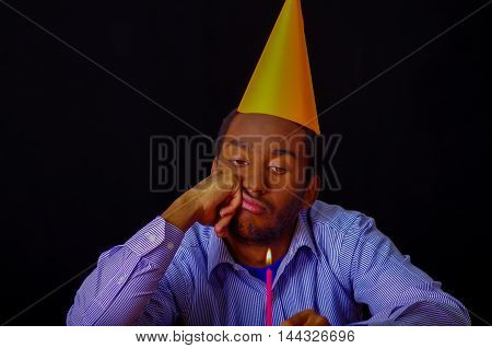 Bored looking man wearing blue shirt and hat sitting by table holding a single candle burning, sad expression facing camera, celebrating alone concept.