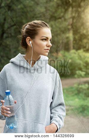 Beautiful woman in sportswear with a bottle of water in park