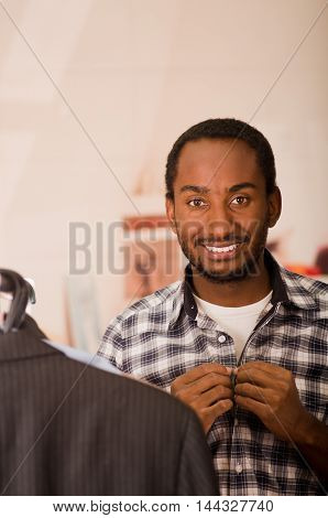 Handsome young man putting on square pattern shirt, buttoning up smiling to camera, fashion concept.