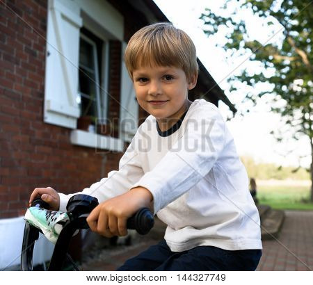smiling boy learning to ride a bicycle