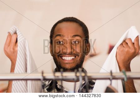 Headshot young man standing behind clothing rack hanger looking into camera, fashion concept.