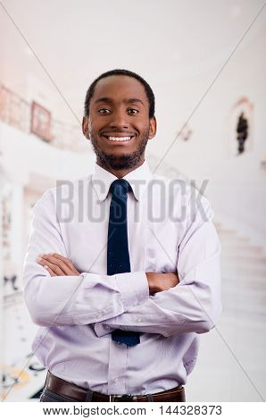 Handsome man wearing shirt and tie posing with arms crossed looking into camera smiling, business concept.
