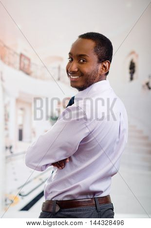 Handsome man wearing shirt and tie posing with his back to the camera, turns head around smiling, business concept.