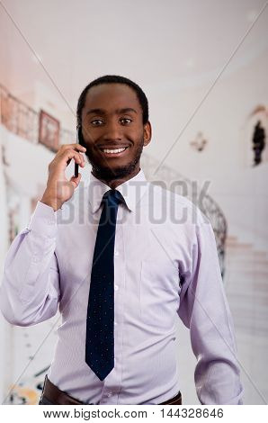 Handsome man wearing shirt and tie standing in lobby area talking on mobile phone, business concept.