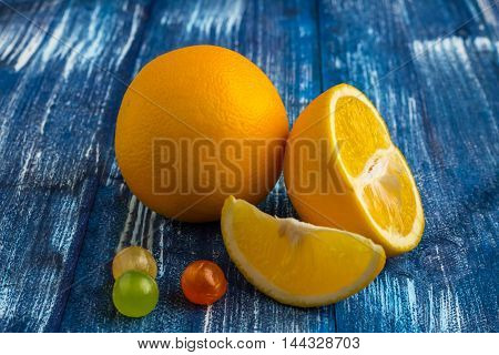 Still life composition of oranges and candies on blue wood