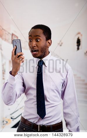 Handsome man wearing shirt and tie holding up mobile phone posing while taking a selfie.