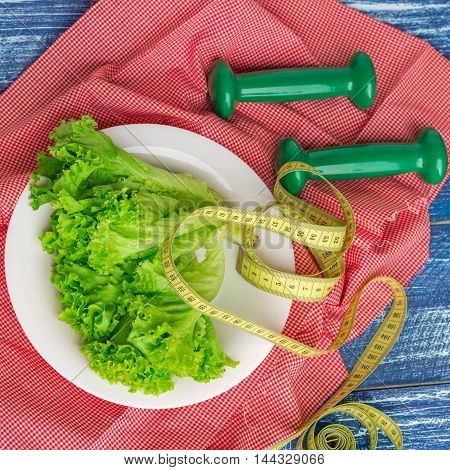 Fitness composition of green lettuce on white plate weights and ruler