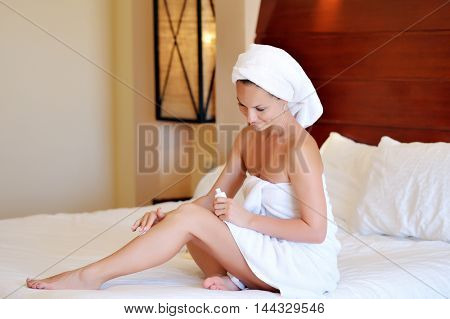 young woman applying cream on her body