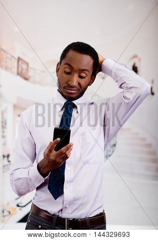 Handsome man wearing shirt and tie posing holding mobile phone in hand while thoughtful body language.