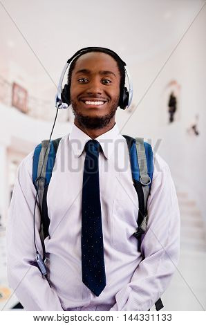 Handsome man wearing headphones with microphone, backpack, white striped shirt and tie smiling to camera, business concept.