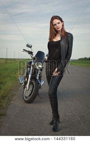 Biker Girl In A Leather Jacket Posing Near Motorcycle