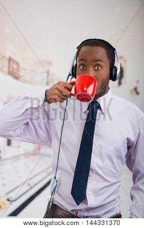 Handsome man wearing headphones with microphone, white striped shirt and tie, drinking from coffee mug, business concept.