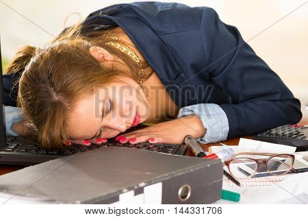 Young woman sitting and lying asleep over office desk with papers, calculator, pens, computer keyboard.