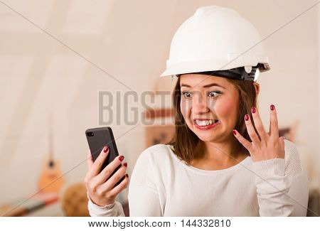 Young woman wearing construction helmet looking at mobile phone with stressed facial expression.