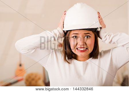 Young woman wearing construction helmet facing camera looking frustrated, upset body language.