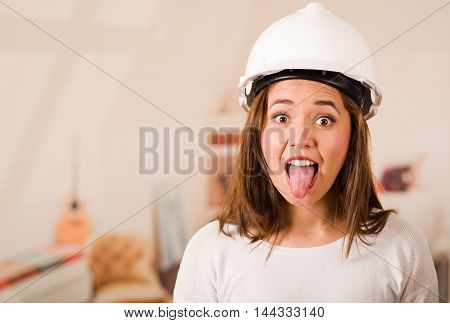 Young woman wearing construction helmet facing camera, holding out tongue making facial expression.
