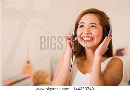 Young woman wearing white top and headset facing camera while interacting smiling, stressed concept.
