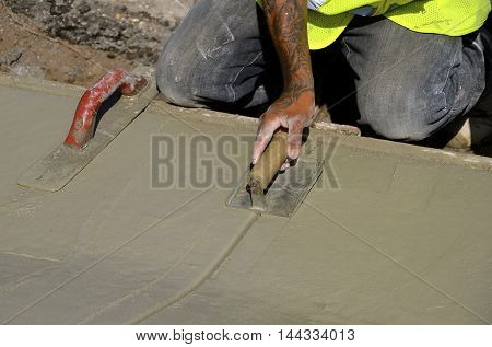 Construction workers trowels wet cement in creating a new curb