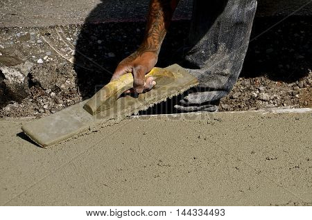 Concrete workers trowels the wet cement as a new curb is created.