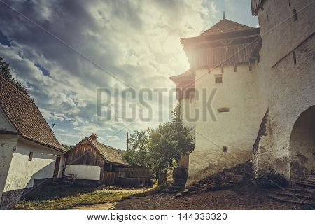 Viscri Romania - July 21 2016: The Viscri fortified church with sun flare effect. The building is listed in 1999 as a UNESCO World Heritage Site Villages with Fortified Churches in Transylvania.