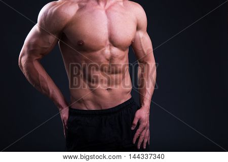 Muscular Body Of Young Man Posing Over Grey