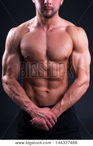 Beautiful Muscular Body Of Young Man Posing Over Grey