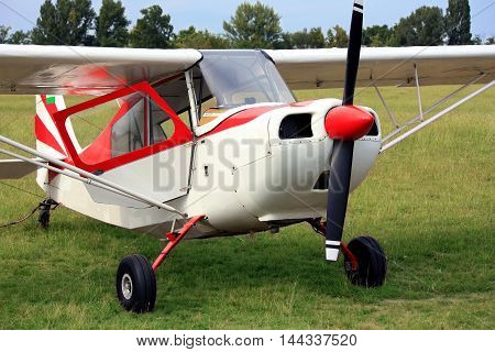 Red glider towing plane on airport grass