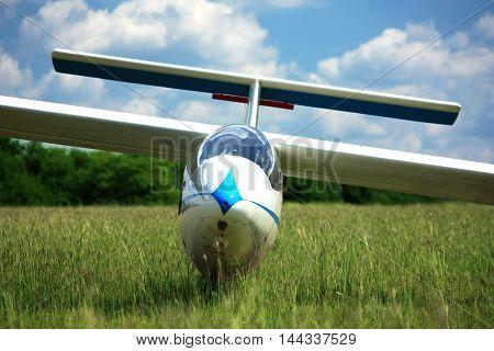 Blue white glider plane on airpoert grass