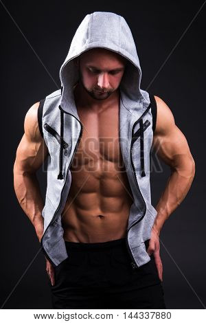 Portrait Of Young Muscular Man In Vest With Hood Over Grey