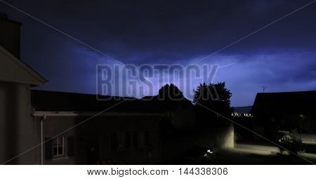 Lightnings in the clouds over the Swiss village