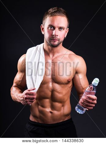 Portrait Of Young Muscular Man Standing Over Grey With Towel And Water