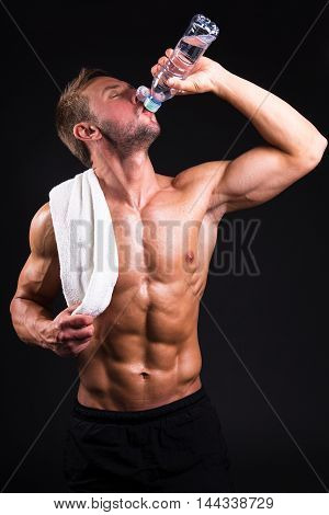Young Muscular Man After Training Drinking Water From The Bottle Over Grey