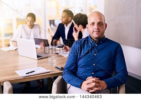 Handsome young caucasian man wearing blue shirt proudly sitting on his chair in front of his production team whom is sitting behind him still busy talking.