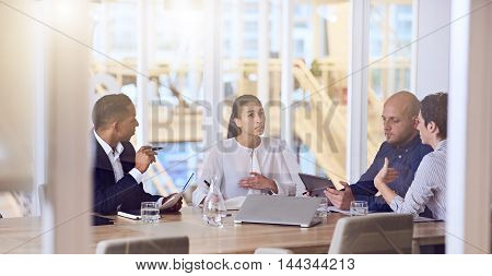 Group of four entrepreneurs with dynamic experience and eclectic backgrounds, all busy working together and talking to one and other during a scheduled weekly meeting.