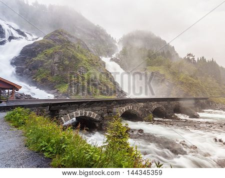 Travel attraction. Powerful twin waterfall Latefoss or Latefossen and six arched bridge along Route 13 Odda Hordaland County in Norway.