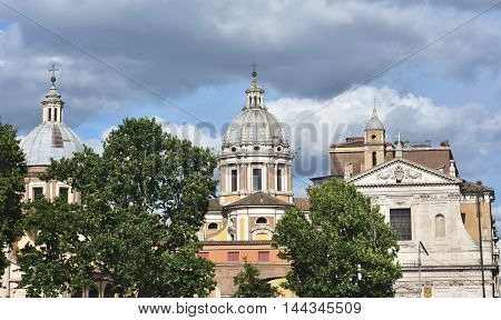 Baroque domes and churches in Rome with cloudy sky seen from River Tiber embankment
