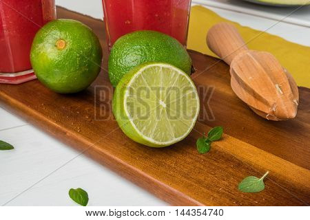 Fresh ripe limes and juicer on wooden table.