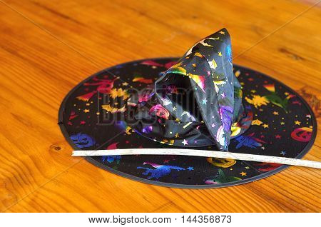 A colorful witches hat displayed with a stick used as a wand