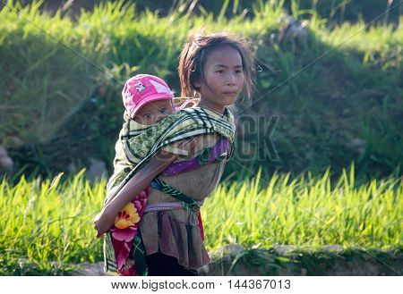 HA GIANG, VIET NAM, July 23, 2016, child carried me on young girl's back, the rice fields. they are ethnic Hmong, Ha Giang mountainous region, Vietnam